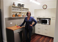 Customer smiling in her newly fitted Q Designs Kitchen